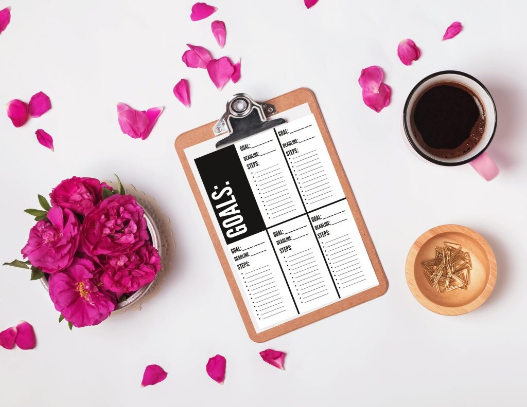 Clipboard with empty paper, coffee and pink roses, top view. Summer mock-up.